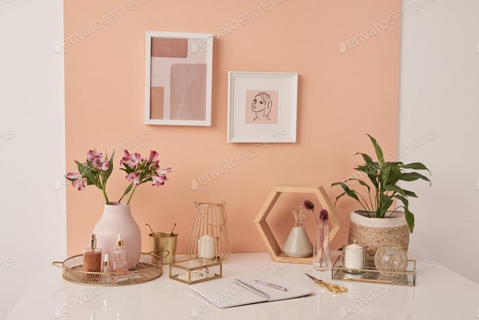 Workplace of interior designer with flowers, beauty products, candles on table