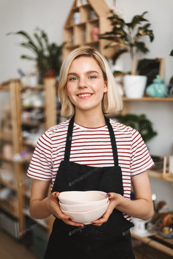 Girl in black apron and striped T-shirt holding handmade bowls in hands happily looking in camera