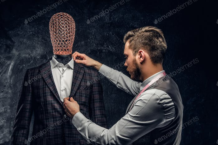 Young fashion designer next to a mannequin in exclusive custom made suit in a dark tailor studio