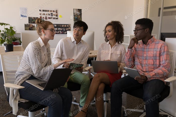 Front view of diverse young business colleagues interacting with each other in modern office