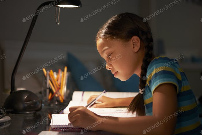 Young Girl Studying At Desk In Bedroom In Evening