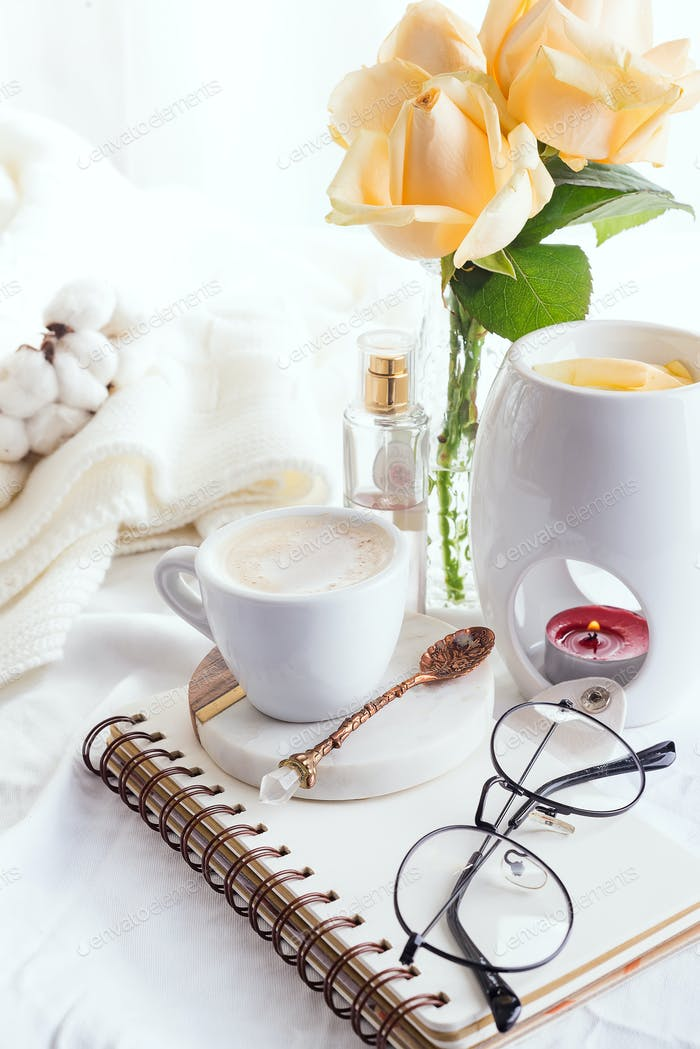 Morning coffee mug with glasses on a notebook, candle and rose on a white bed top view . Woman cozy
