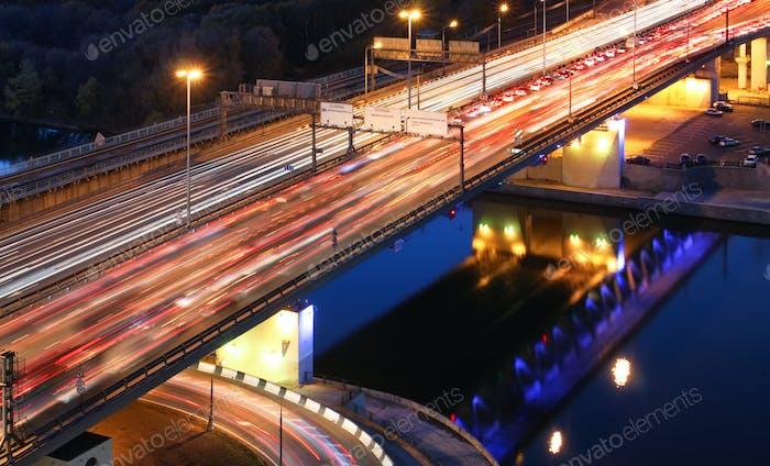 Straßenbrücke über den Fluss in der Nacht, Blick von oben. Lichtwege von Autos auf einer Autobahn.