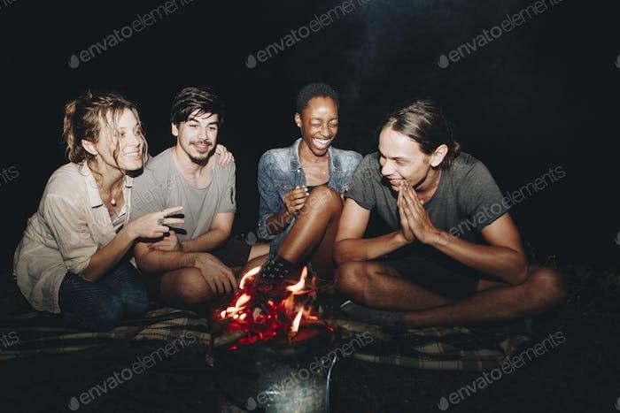 Gruppe von jungen erwachsenen Freunden sitzen rund um das Lagerfeuer im Freien