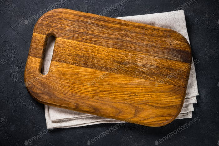 Black wooden cutting board on black table