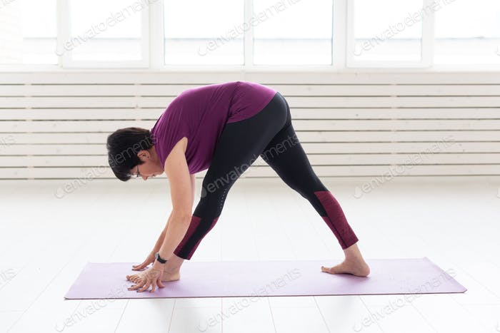 People, sport and healthcare concept - Middle-aged woman practicing yoga, standing in stretching