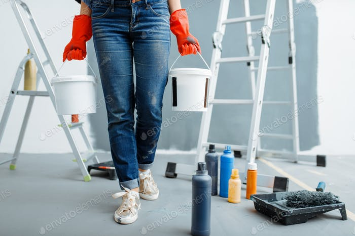 Female house painter holds pails with paints