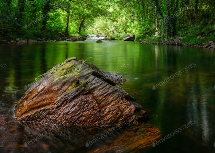Reddish rock in the middle of a river