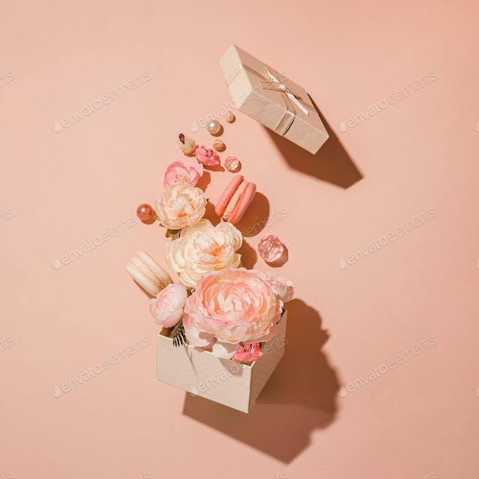 Blumenexplosion, Blumen in Bewegung aus Geschenkbox vor Pfirsichhintergrund