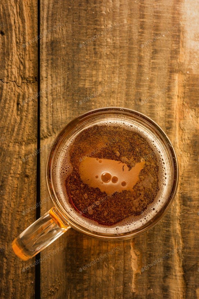 Amerikanisches Bierkonzept, USA Silhouette auf Schaumstoff in Bierglas auf Holztisch.