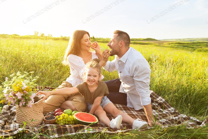 Young woman feeding her man with grape