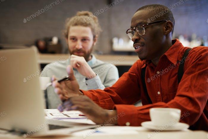 Junge afrikanische Geschäftsmann mit Laptop