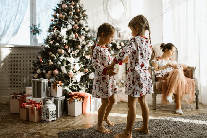 Two little sisters in pajamas having fun New Year's tree with gi
