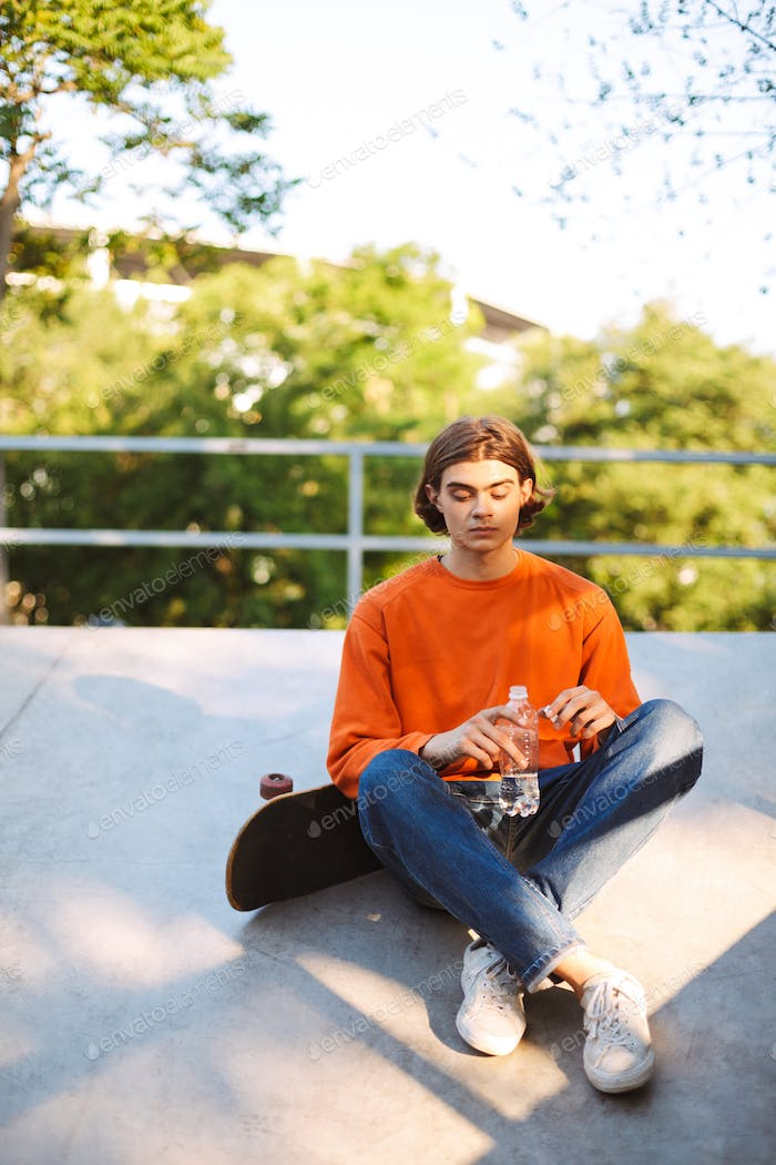 Young guy in orange pullover with skateboard holding bottle of w