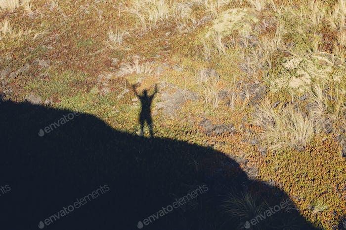 Erhöhte Ansicht des Schattens des Menschen mit erhobenen Armen, stehend auf Hügel