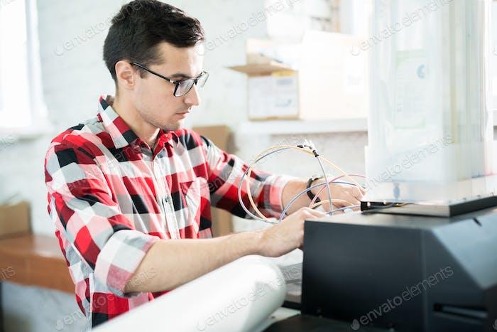 Busy engineer repairing printer in office of printing company