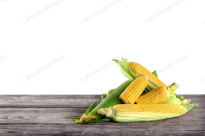 Mais auf einem Holztisch isoliert auf weißem Hintergrund