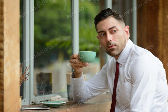 Handsome businessman thinking while drinking coffee at the coffee shop