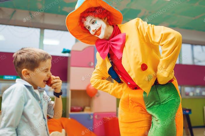 Lustiger Clown Animator tanzen mit kleinen Jungen