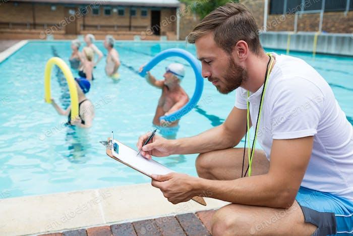 Swim coach writing on clipboard