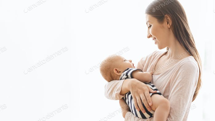 Adorable infant baby in the arms of his mom over white background