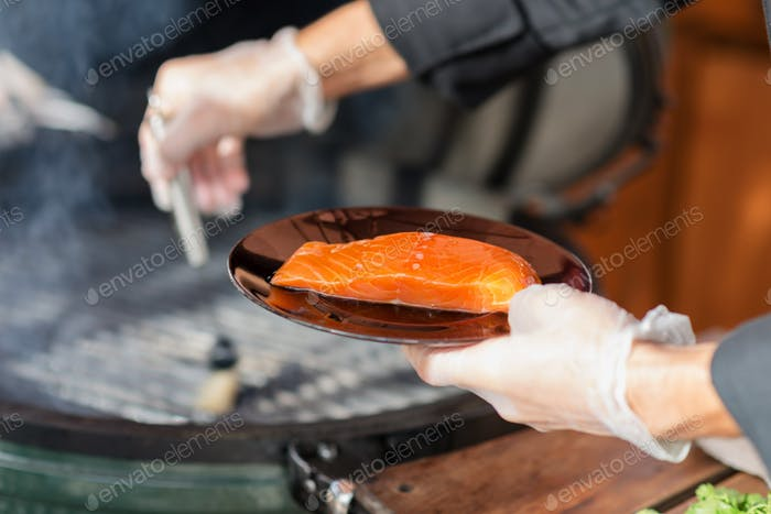stages of cooking salmon on the grill - the chef puts a piece of fresh fillets on grill rack