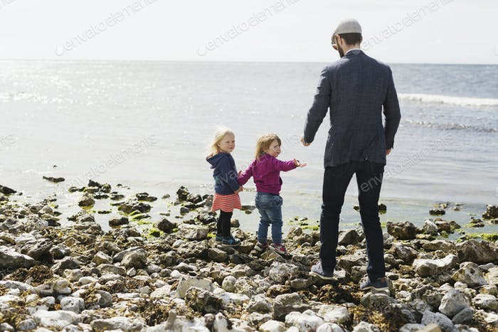 Man giving pebbles to daughter at beach