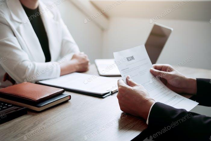 Bewerber halten ein Lebenslaufdokument im Vorstellungsraum, Vorstellungsgespräch.