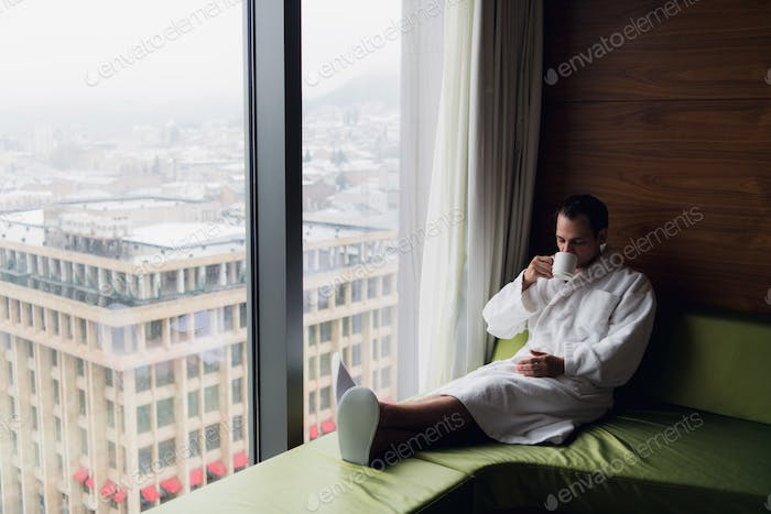 Attractive Man enjoying his morning coffee on his computer at his hotel room