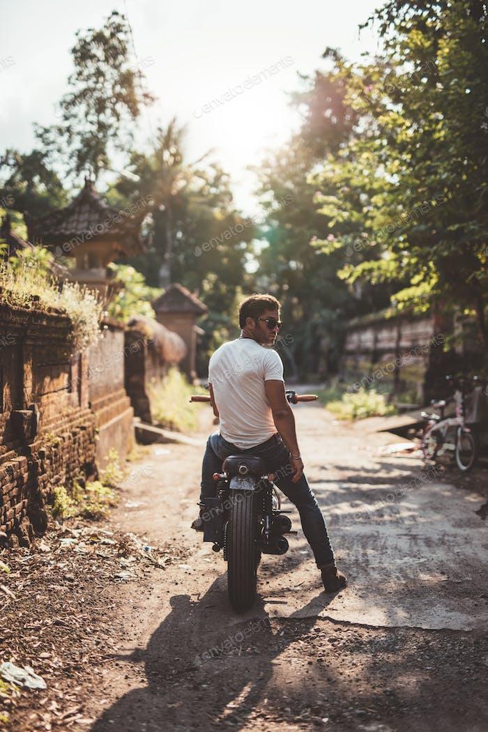 Junger Mann sitzt auf seinem Motorrad