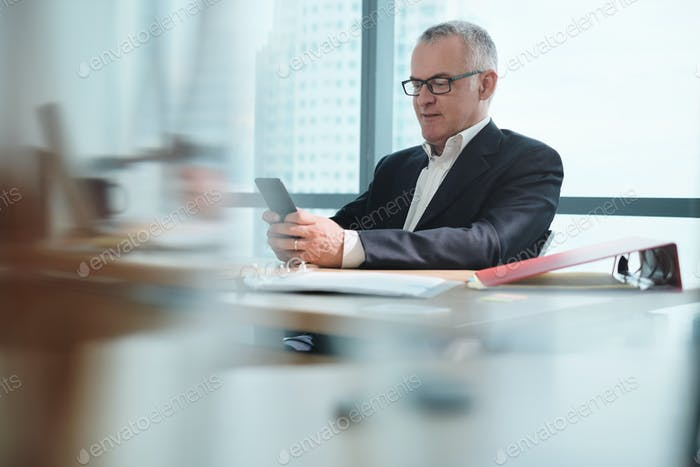 Business Man In Office Using Social Media During Working Hours