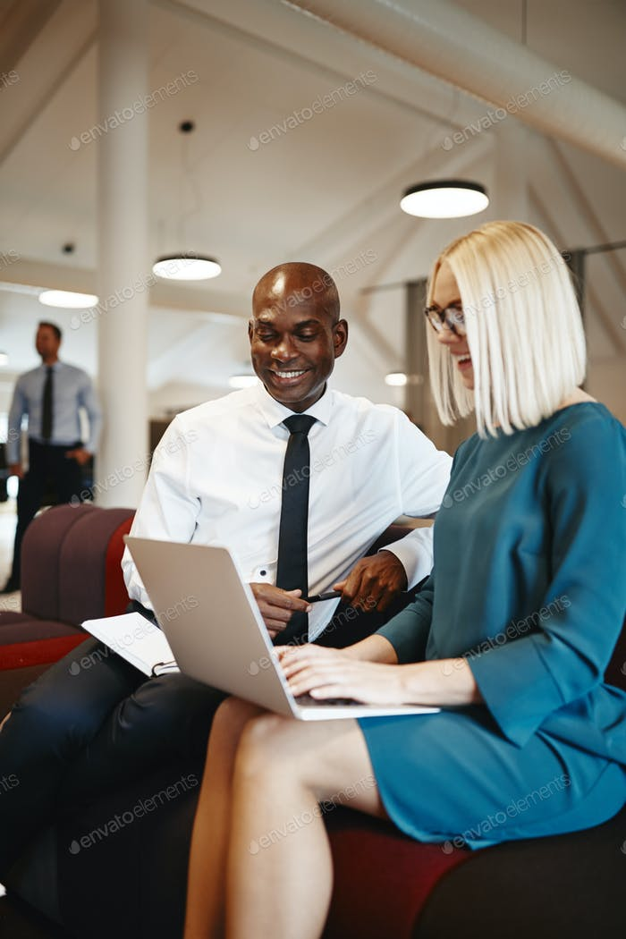 Smiling business coworkers discussing work together on an office sofa