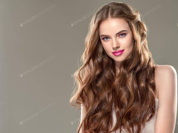 Beautiful brunette woman with eyelashes extension and long brunette curly hairstyle pink lipstick