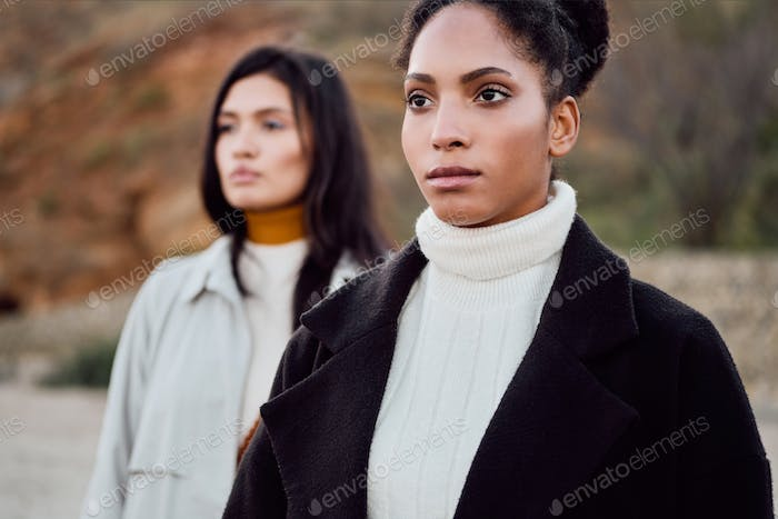 Beautiful stylish African American girl thoughtfully looking away with friend outdoor