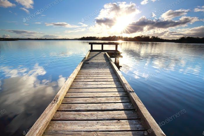 Sonnenschein über langen hölzernen Pier am See