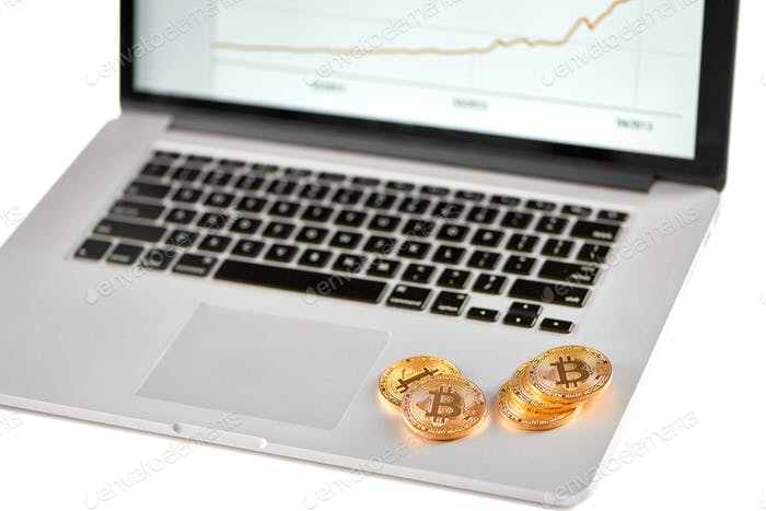Stack of golden bitcoins placed on silver laptop with blurred financial chart on its screen
