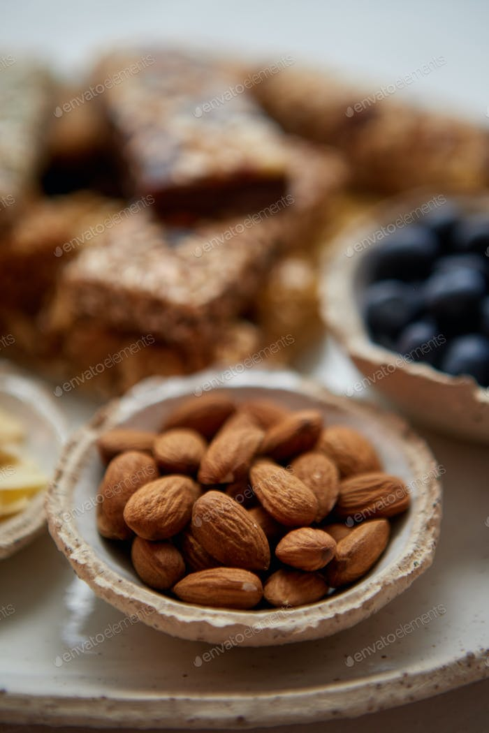 Close up of whole Almonds. With various energy nutrition bars in background