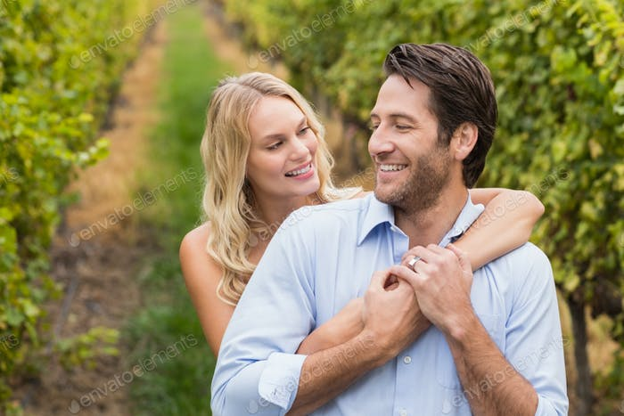 Young happy couple embracing each other in the grape fields