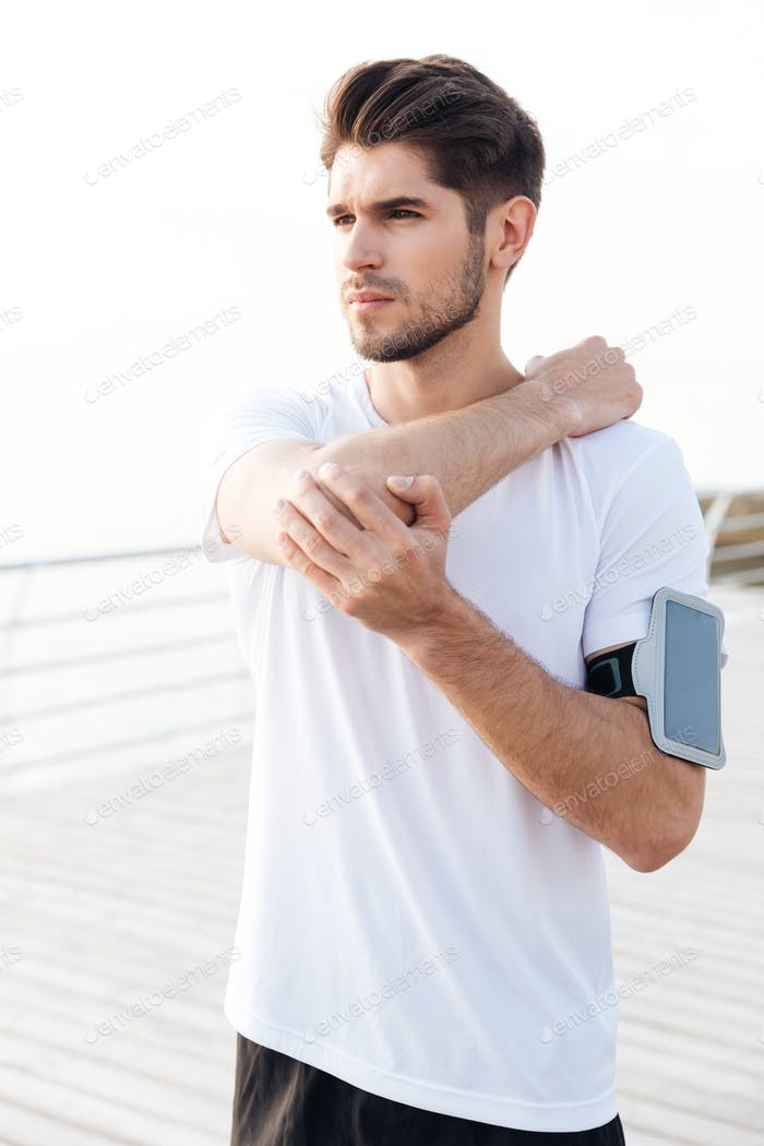 Man athlete with mobile phone in armband stretching arms