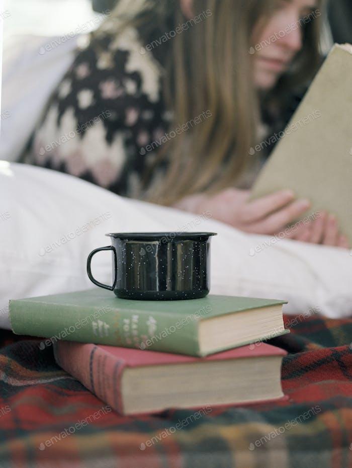 Junge Frau liest ein Buch, einen Becher, der auf zwei Büchern steht.