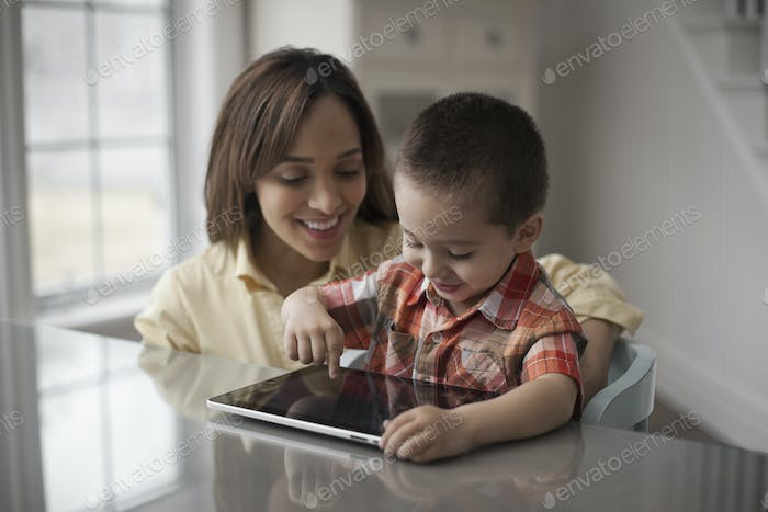 A mother and child looking at the screen of a digital tablet, the boy touching the screen.