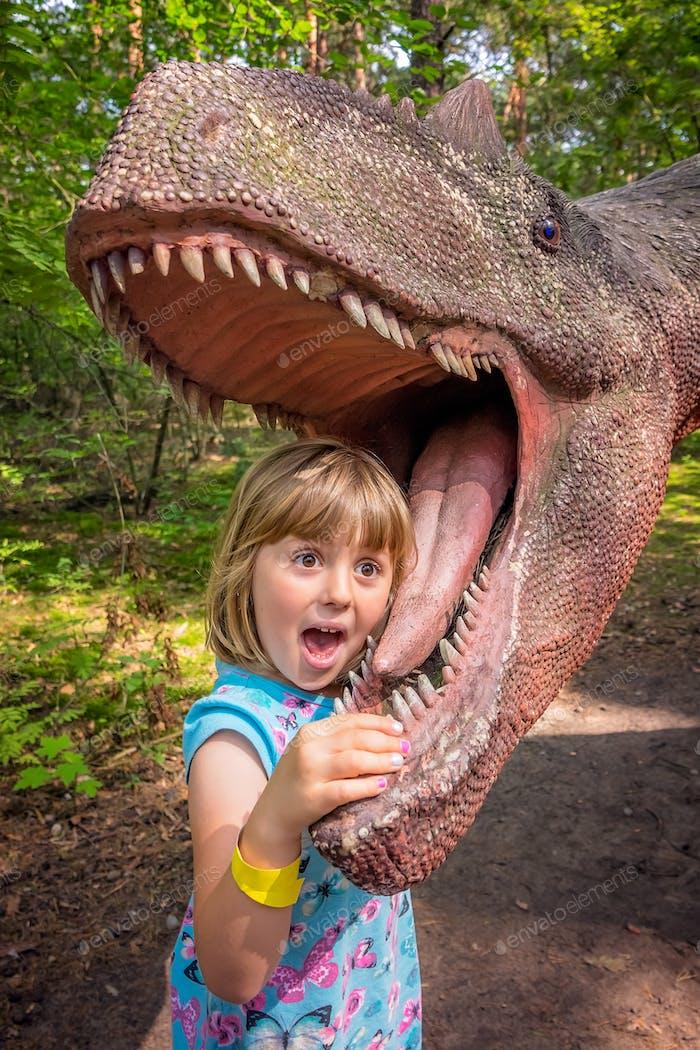 Kleine Mädchen Kopf in den Mund eines Dinosauriers