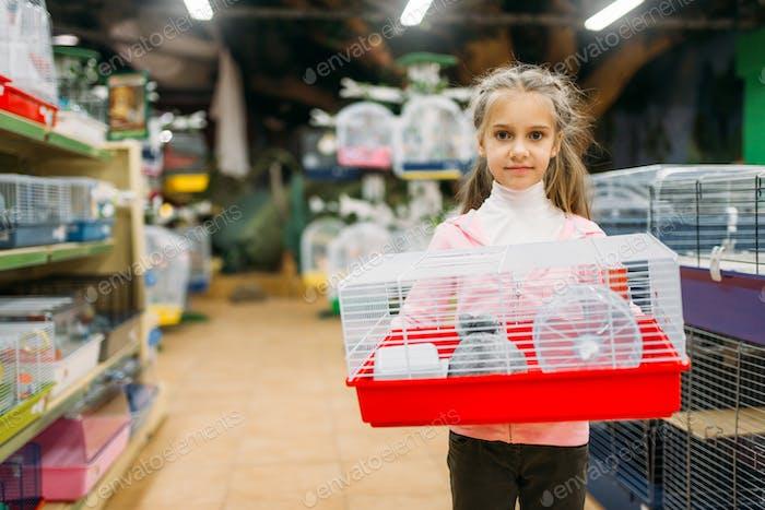 Маленькая девочка держит клетку для хомяка в зоомагазине