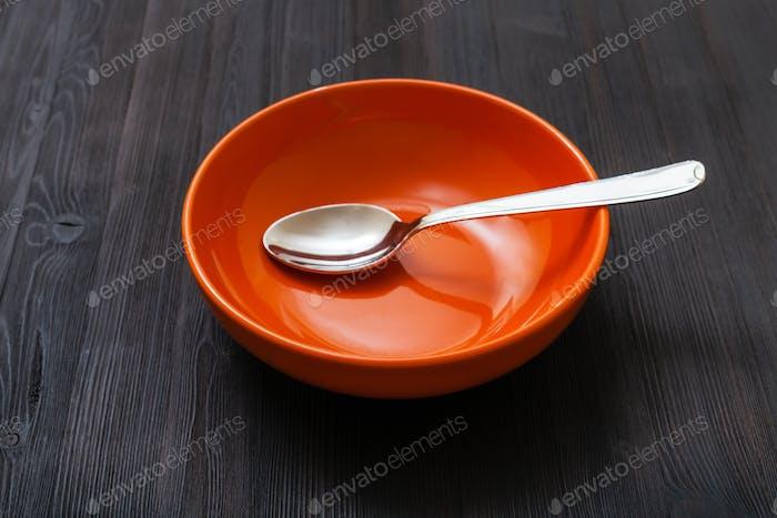 orange Schüssel mit Löffel auf dunkelbraunem Brett