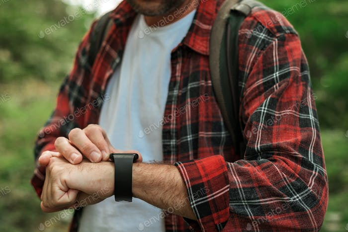 Smart watch on male hiker hand while hiking in woods