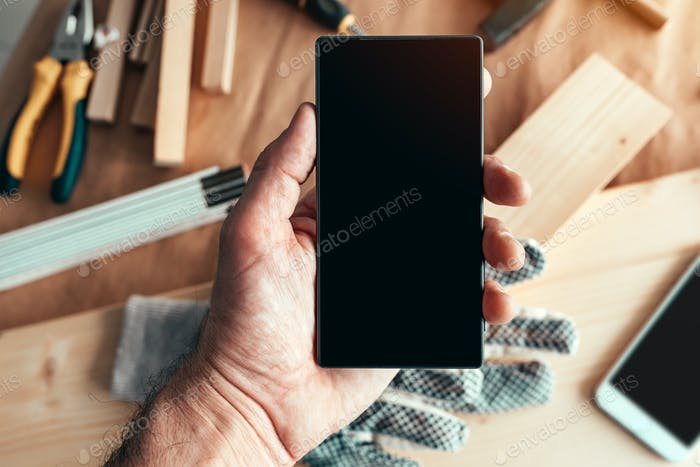 Handyman maintenance worker holding smartphone with blank mock u