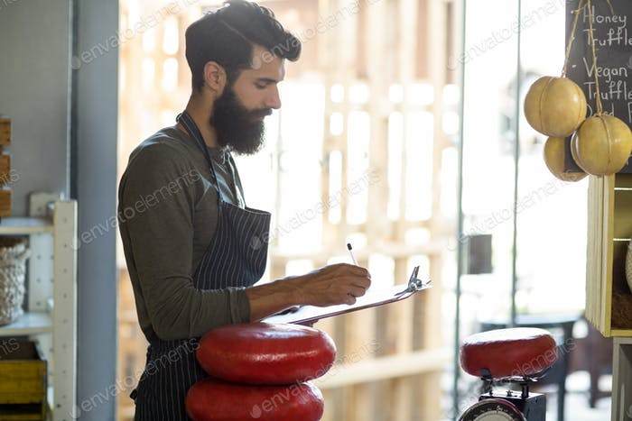 Salesman writing on clipboard at counter