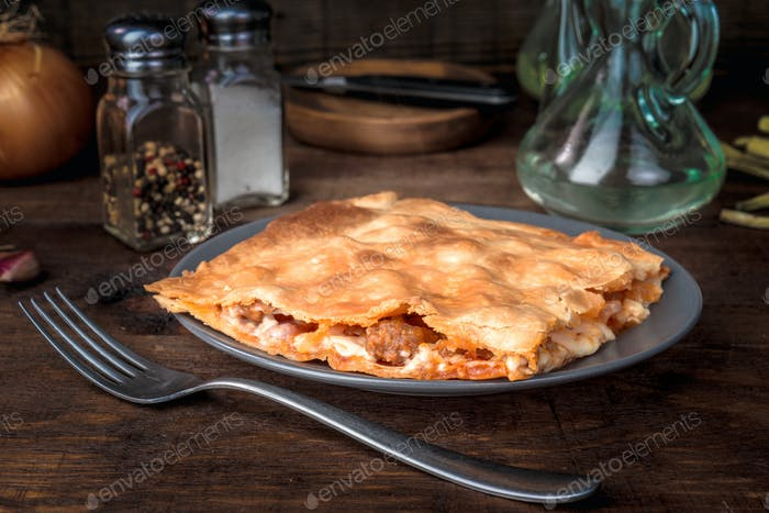 portion of sausage and tomato pie, on dark wooden board