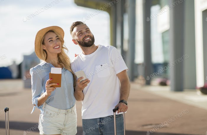 Couple standing near airport with their baggage