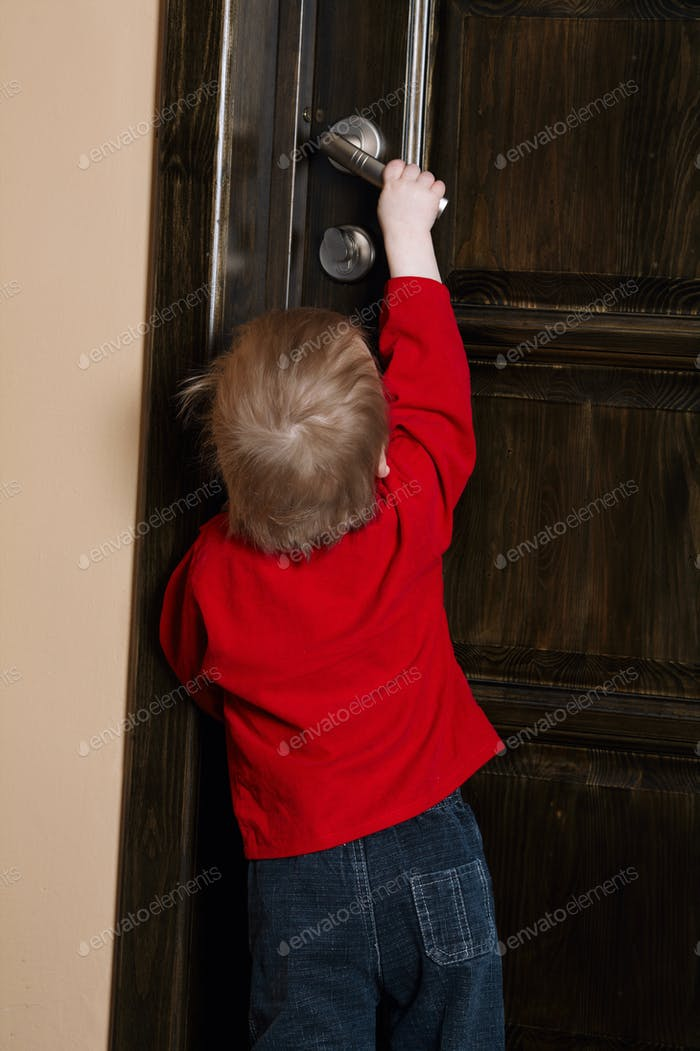 little boy tries to open door